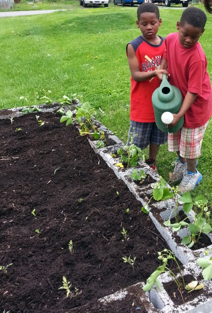 Neighbor kids came out to help water the newly planted seeds and plants.